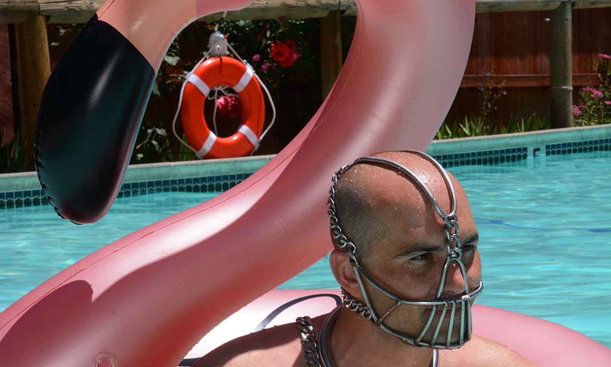 Boundless attendee wearing face cage in pool with inflatable flamingo